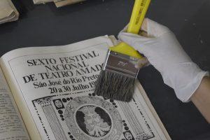 Uma página de jornal sendo higienizado por uma trincha/pincel.